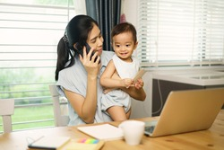 Work from home. Asian young mother calling mobile, working and holding her son. Entrepreneur woman working with laptop. A boy sitting with mom at home in kitchen. quarantine on coronavirus pandemic.