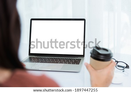 Work from home, Back of Asian young businesswoman video conference call or facetime meeting online hold coffee cup on front laptop computer quarantines disease coronavirus or COVID-19 at home office