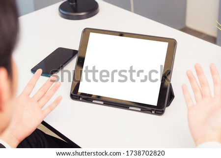 Work from home, Back view of Asian young businessman smile wearing suit video conference call or facetime by smart digital tablet computer blank screen raise his hand explain to teammates on desk