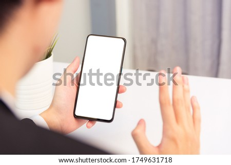 Work from home, Back view of Asian young businessman smile wearing suit video conference call or facetime by smart digital mobile phone blank screen raise hand to say hello teammates on desk