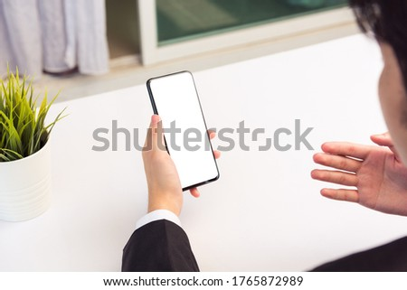 Work from home, Back view of Asian young businessman smile wearing suit video conference call or facetime by smart digital mobile phone blank screen raise his hand to explain to teammates on desk