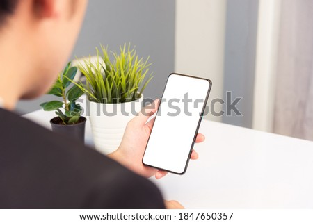 Work from home, Back view of Asian young businessman smile wearing suit video conference call or facetime by smart digital mobile phone blank screen listen carefully to your co-workers on desk