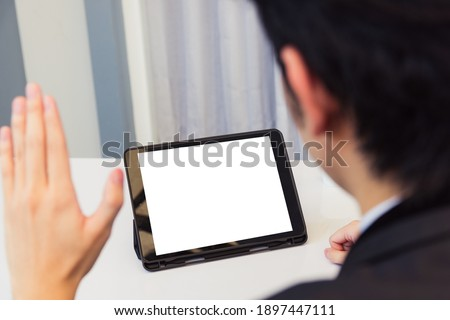 Work from home, Back view of Asian young businessman smile wearing suit video conference call or facetime by smart digital tablet computer blank screen raise hand say hello to teammates on desk