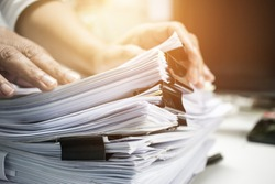 Work from Home, Businessman hands working in Stacks of paper files for searching information on work desk home office, business report papers,piles of unfinished documents achieves with clips indoor.
