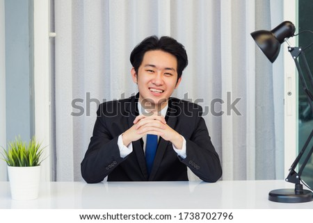 Work from home, Close up face of Asian young businessman video conference call or facetime he looking to camera sitting and holding hands to listen to colleagues explain the work on desk at office