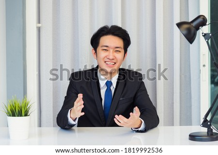 Work from home, Close up face of Asian young businessman video conference call or facetime he looking to camera raises hands to explain about his job to team on a desk at the home office