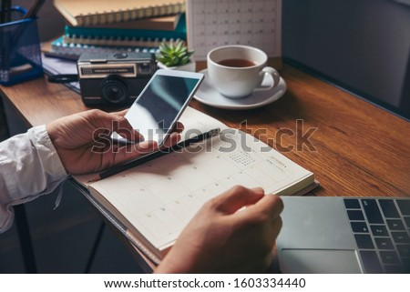 Work from home concept. Planner using phone and laptop to plan daily agenda on calendar book. Woman Hand mark and note schedule (holiday trip) on diary at business office desk. Coffee place on table.