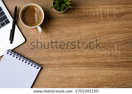 Photo of  Work from home. desk office with laptop, blank notepad, coffee cup and pen on wood table. Flat lay top view copy spce.