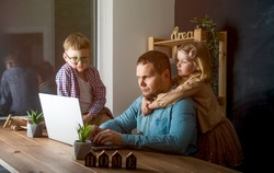 Work from home. Man works on laptop with children playing around. Family together