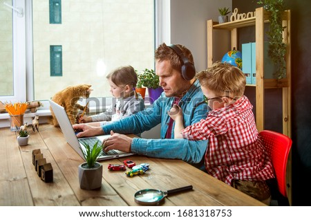 Work from home. Man works on laptop with children playing around. Family together with pet cat on table