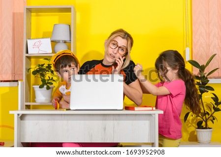 Work from home. Mother work on laptop with children playing around. Children make noise and disturb mom at work.
