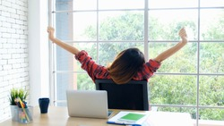 Work from home, Stretch for relax, Young asian woman stretching body while working with laptop computer at her desk home office, Back of female student raised arms take rest from online education