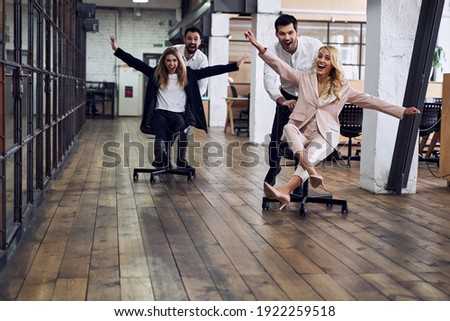 Work hard play hard. Four young cheerful business people in formal wear having fun while racing on office chairs and smiling