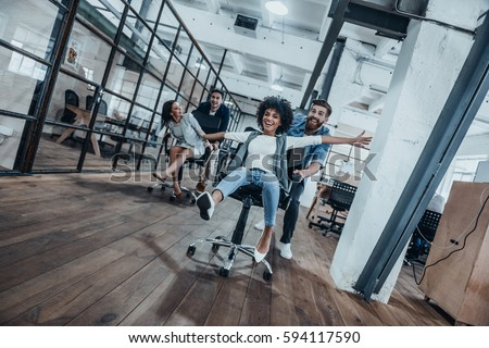 Work hard play hard! Four young cheerful business people in smart casual wear having fun while racing on office chairs and smiling #594117590
