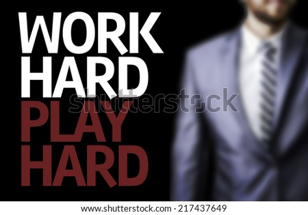 Work Hard Play Hard written on a board with a business man on background #217437649
