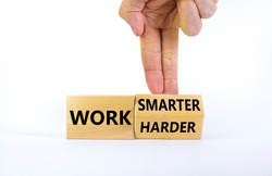 Work harder or smarter symbol. Businessman turns wooden block and changes words 'work harder' to 'work smarter'. Beautiful white background, copy space. Business and work harder or smarter concept.