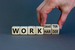 Work harder or smarter symbol. Businessman turns wooden cubes and changes words 'work harder' to 'work smarter'. Beautiful grey background, copy space. Business and work harder or smarter concept.