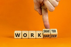 Work harder or smarter symbol. Businessman turns wooden cubes and changes words 'work harder' to 'work smarter'. Beautiful orange background, copy space. Business and work harder or smarter concept.