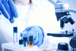 Work in chemical laboratory, test tubes with chemical liquids, microscope, vaccine development