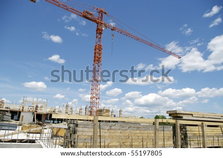 work in progress, construction site with crane in the background against the sky and clouds and lumber wood stockpile in the foreground.