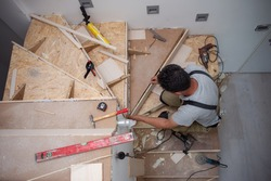 work in progress on stylish interior professional carpenter installing wooden stairs in big modern two level luxury apartment