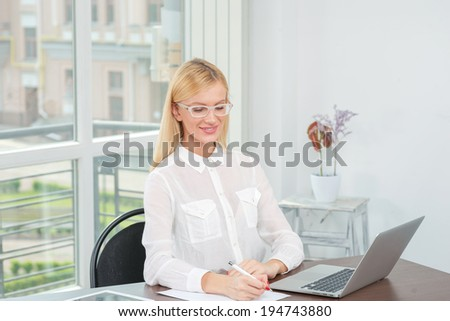 Work in progress. The friendly and confident young woman sitting at a laptop and works at the table. Successful businesswoman writing on a sheet of paper