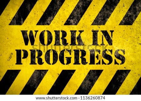 Work in progress warning sign stencil with yellow and black stripes painted over concrete wall cement texture background. Concept for do not enter the area, caution, danger, construction site. #1136260874