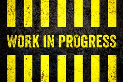Work in progress warning sign with yellow and black stripes painted over cracked concrete wall coarse texture background. Concept for do not enter the area, caution, danger, construction site.