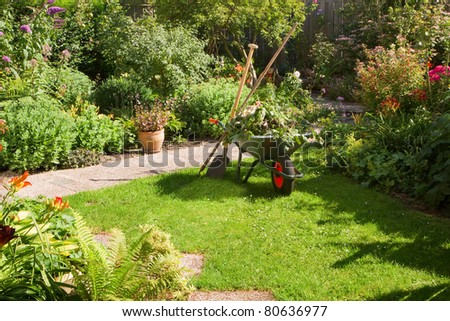 Work in summer garden in the morning with wheelbarrow, shovel and rake - horizontal