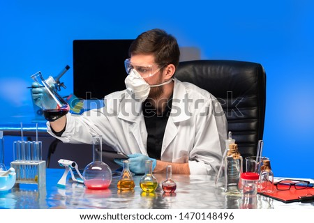 Work in the chemical laboratory. The chemist evaluates the results of the experiment. Experiments with dangerous liquids. Examination of food products. Chemical equipment on the table