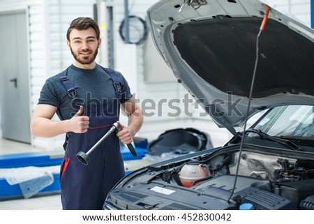 Work is done. Shot of a handsome car mechanic smiling to the camera showing thumbs up posing near a car he is working on #452830042