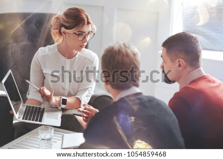 Work issues. Good looking attractive smart businesswoman holding a laptop and pointing at its screen while discussing work issues with her male colleagues