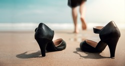 Work Life Balance Concept. Business Woman take off her Working Shoes and leave it on the Sand Beach for Walk into the Sea on Sunny Day. Quit a Job, Office Outing or Summer Vacation. Low angle View