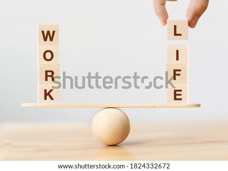 Photo of  Work life balance concept. Wooden cube block with word WORK and LIFE on seesaw