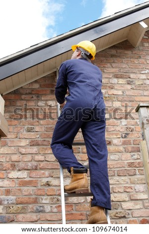 Work man climbing a ladder at the side of a house