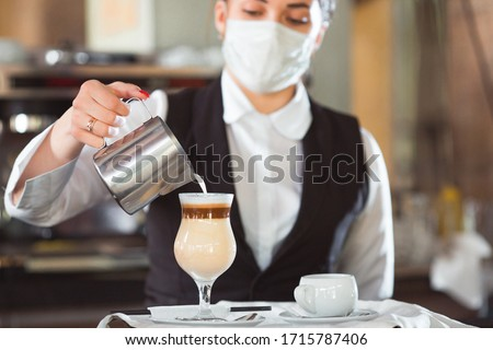 work of a waiter in a restaurant in a medical mask