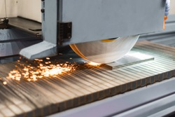 Work of an industrial surface grinding machine. Grinding of a flat metal part. Sparks fly out from under the grinding wheel.