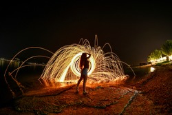 Work of fire sparks from spinning steel wool by human behind of a girl.