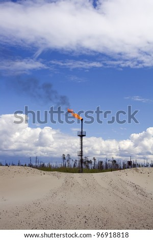 Work of oil and gas industry. Flame torch. Colorful blue sky with white clouds