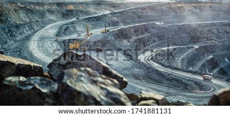 Work of trucks and the excavator in an open pit on gold mining, soft focus
