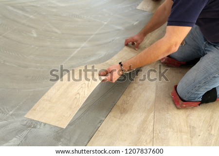 Work on laying flooring. Worker installing new vinyl tile floor. #1207837600