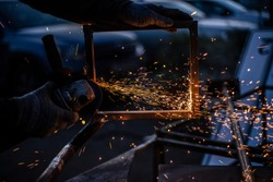 Work on metal. The master cuts metal. Grinding the surface with a circular saw. Sparks fly due to strong friction. Work in the garage.
