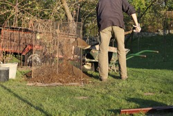 Work on the garden at sunset. Man in working clothes going to sieving earth. Green wheelbarrow full of clay next to sifter or screen. Sieve earth will be used as next generation of plants.