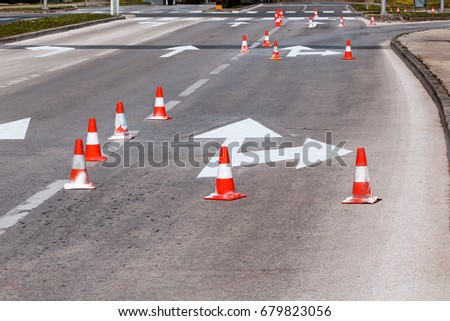 Work on the road. Street signs and road marking. Traffic signs for signaling. Road maintenance, under construction sign and traffic cones. Road block with white arrow showing alternate way. #679823056
