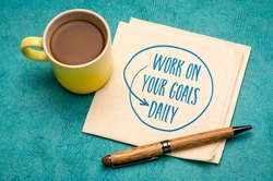 work on your goals daily - motivational reminder, handwriting on a napkin with a cup of coffee, goal setting, business and personal development concept