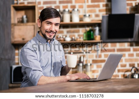 Work online. Joyful young handsome man drinking coffee while working online #1118703278