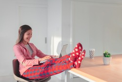 Work online remote from home funny concept. Asian woman relaxing in pajama pants and cozy socks while wearing professional top and suit for videocall meeting.