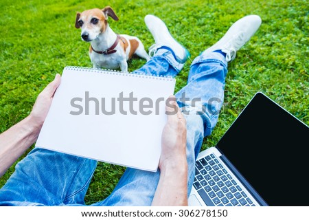 Work outside. Nature and fresh air. Dog and man with white paper note book and pc