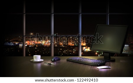 Work place in the office at night with a city view from window - stock photo