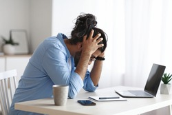 Work Problems. Millennial Freelancer Guy Siting At Desk And Touching Head In Despair, Having Luck Of Inspiration While Working On Laptop At Home Office, Depressed Eastern Man Got Bad News, Copy Space